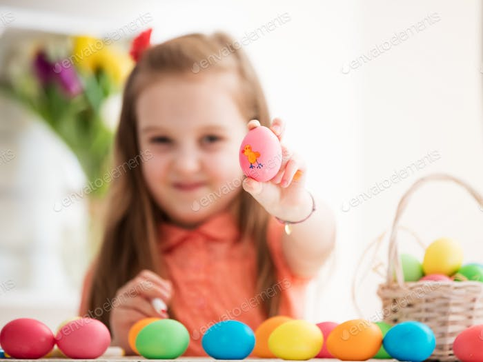 Young girl showing drawing on an egg.