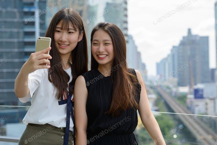 zwei glücklich junge schön asiatische Teenager-Mädchen nehmen selfie zusammen gegen Ansicht der Stadt