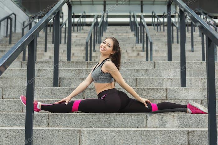 Sporty girl sitting in split on stadiumn steps