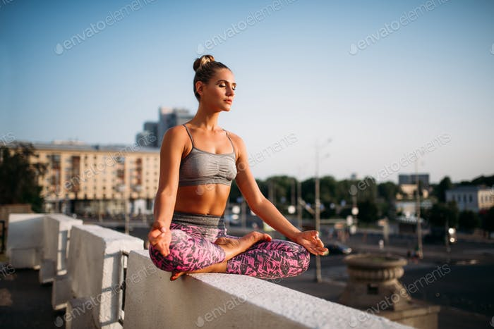 Young woman in yoga pose, city on background