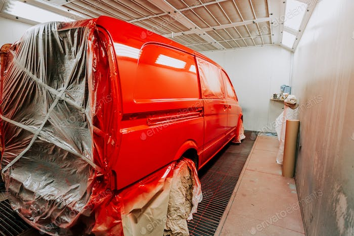 Red van in paint booth. Car workshop details, painting of a car