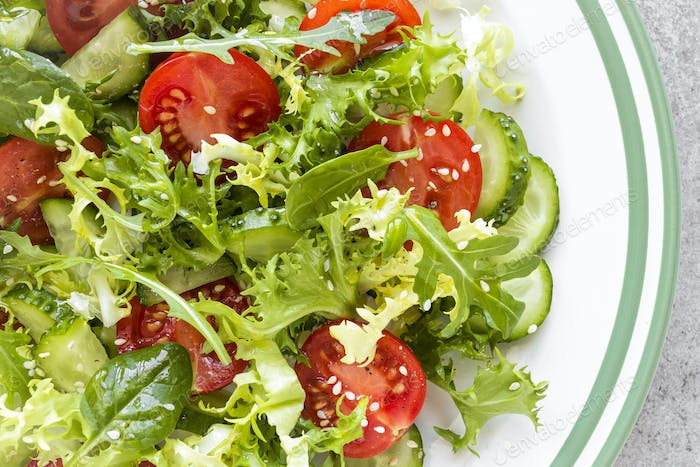 Healthy vegetable salad of fresh tomato, cucumber, spinach, frize and sesame on plate. Diet menu