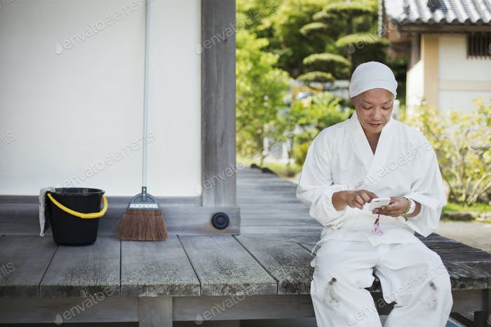 Buddhist monk wearing white robe sitting on wooden floor outside a temple, using mobile phone.
