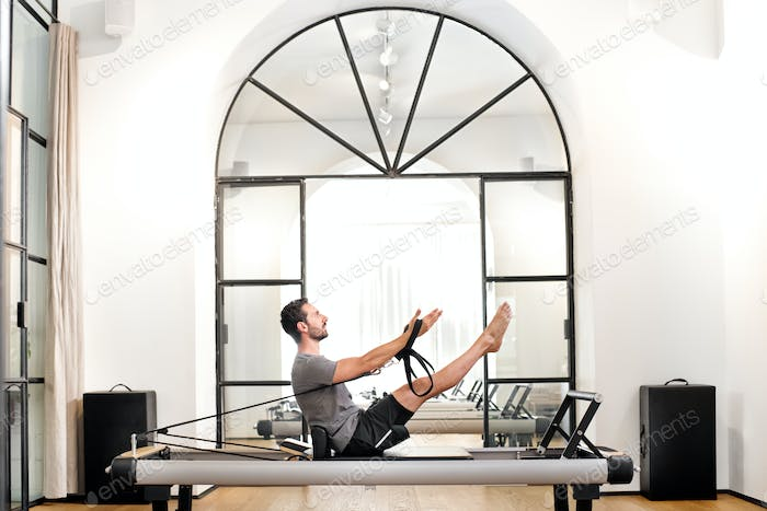 Man performing pilates teaser exercise in a gym