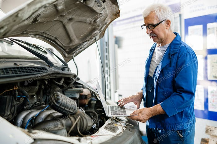 Senior man with laptop standing by engine of broken machine in workshop