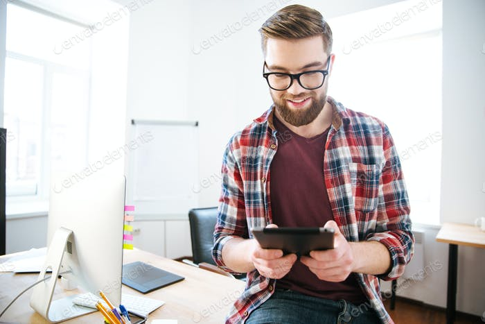 Happy handsome man with beard sitting and using tablet