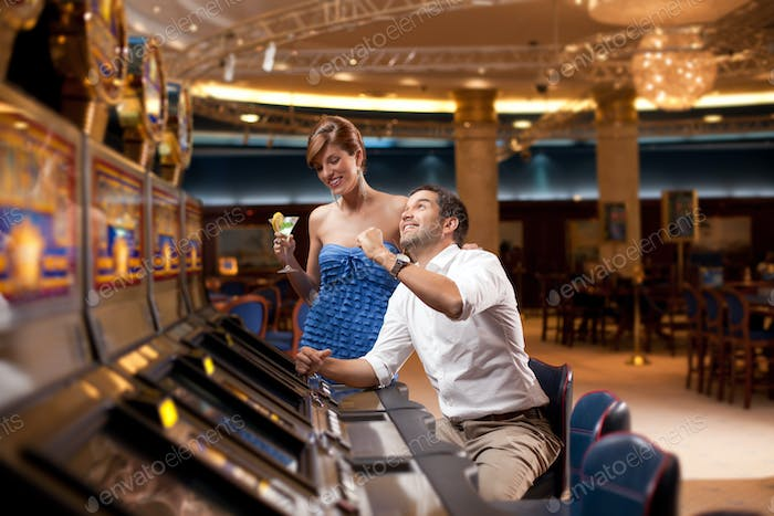 man and woman playing he slot machine