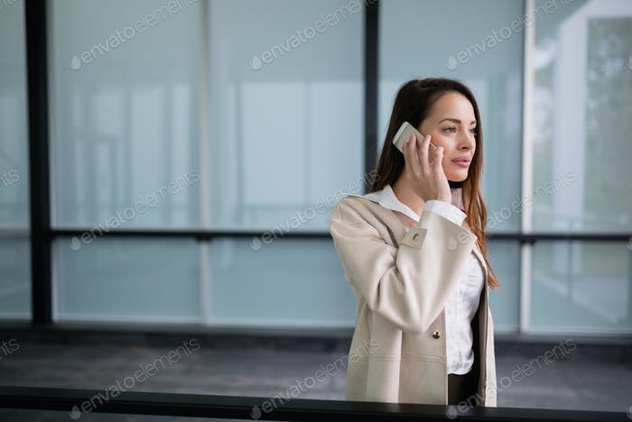 Businesswoman using phone outdoors