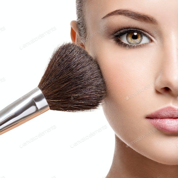 Frau Anwendung trockenen kosmetischen Pulver auf dem Gesicht