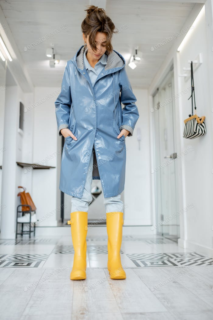 Woman wearing yellow boots and raincoat at the hallway