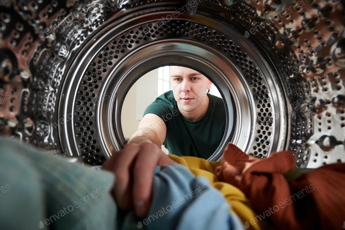 View Looking Out From Inside Washing Machine As Young Man Does Laundry