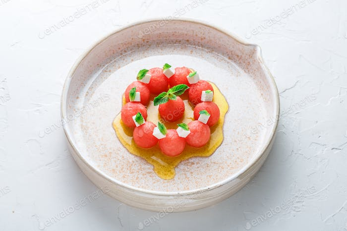 Watermelon salad with feta cheese and mint with olive oil, restaurant meal.