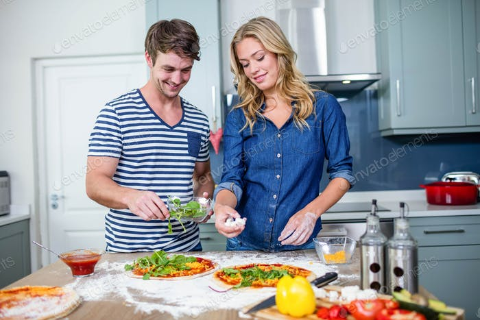 Smiling couple preparing pizza in the kitchen