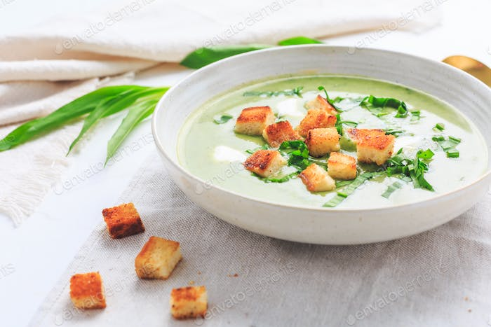 Ramson or bear leek soup with crouton and sour cream