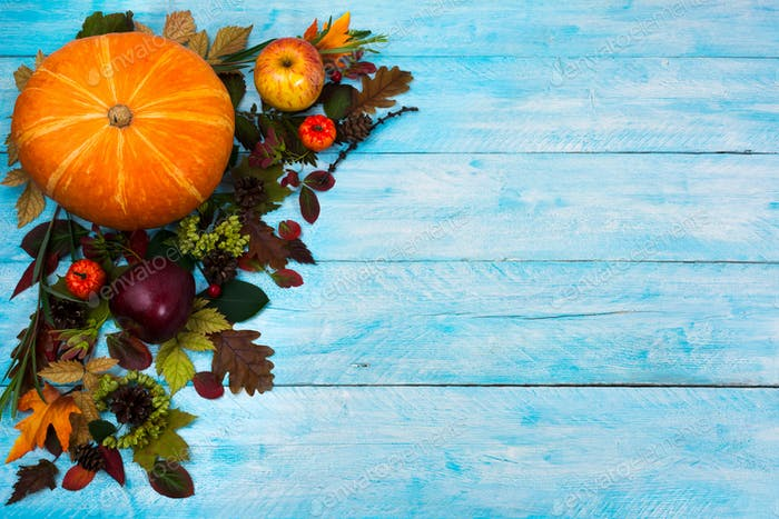 Happy Thanksgiving  greeting with fall leaves on blue wooden bac