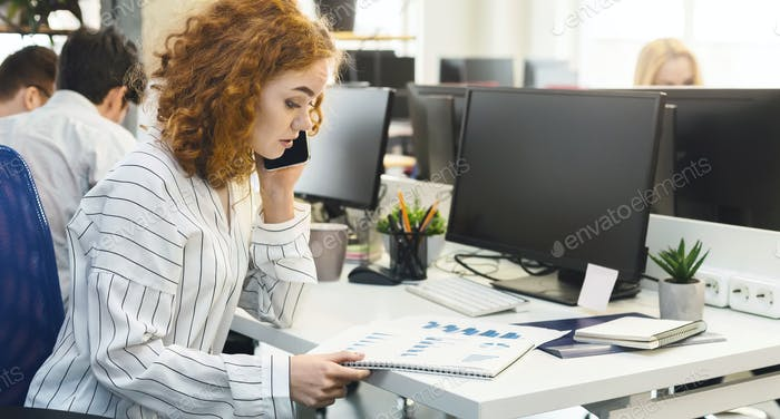 Woman sales manager talking on cellphone and reading graphs