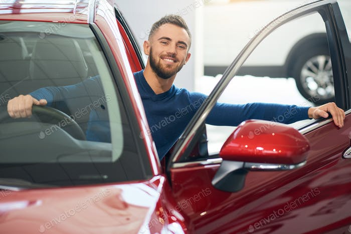Happy man sitting in car in dealership