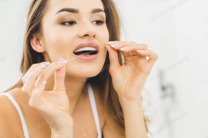 Porträt einer schönen Frau, die Zähne mit Zahnseide putzt