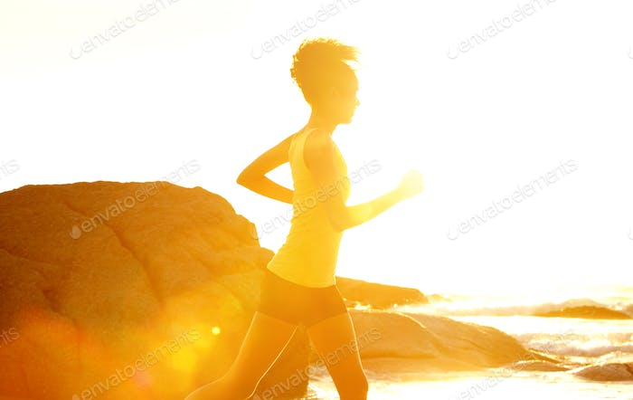 Young fitness woman running by the sea