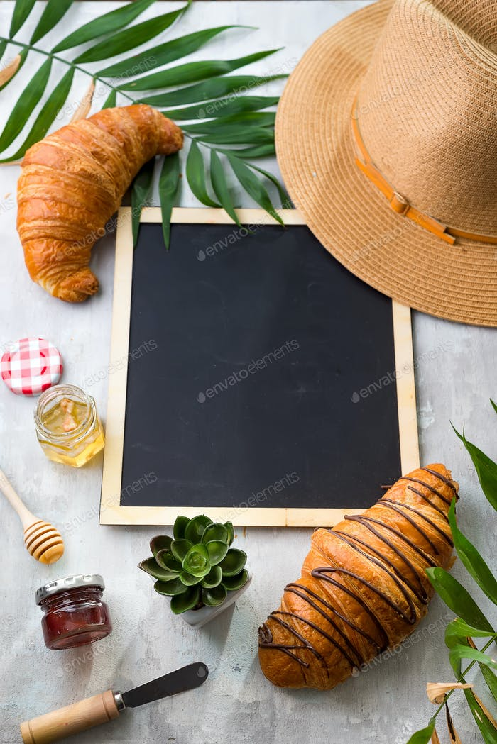 breakfast with croissants, honey, jam and berries on the trip. Background of a chalkboard