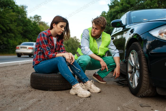 Young couple repair flat tyre, car breakdown