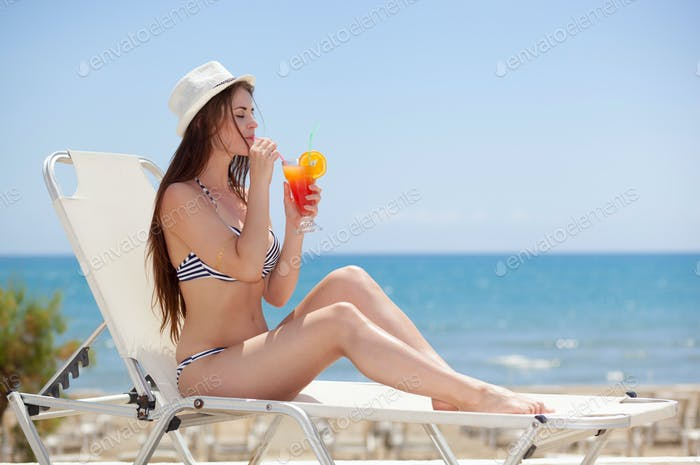 Woman with cocktail during sunbathing on a summer day in the tropics