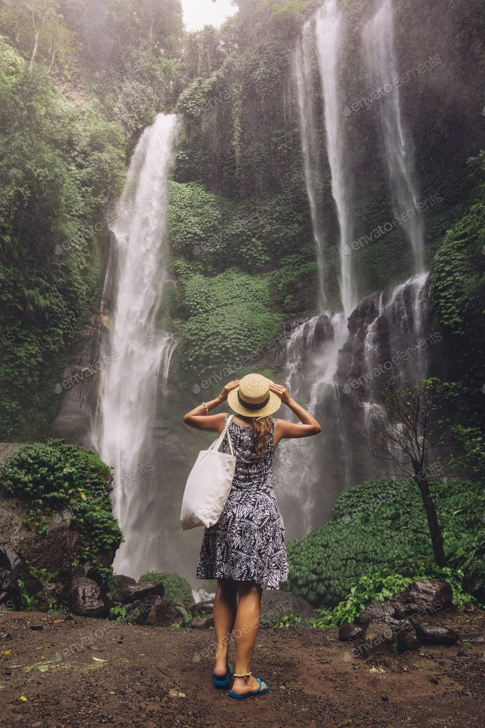 Female tourist admiring waterfall in rain forest