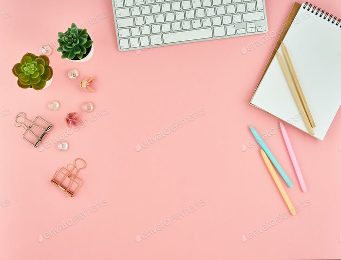 Top view of modern pink woman office desktop with blank notepad, computer. Mock up, empty space.