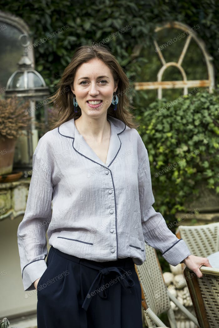 Woman with brown hair and wearing grey blouse standing outdoors, smiling at camera.