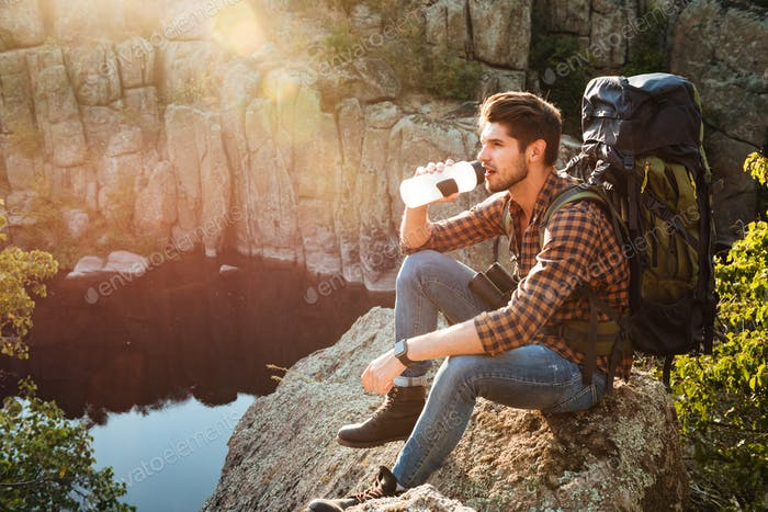 Adventure man with water sitting on rock