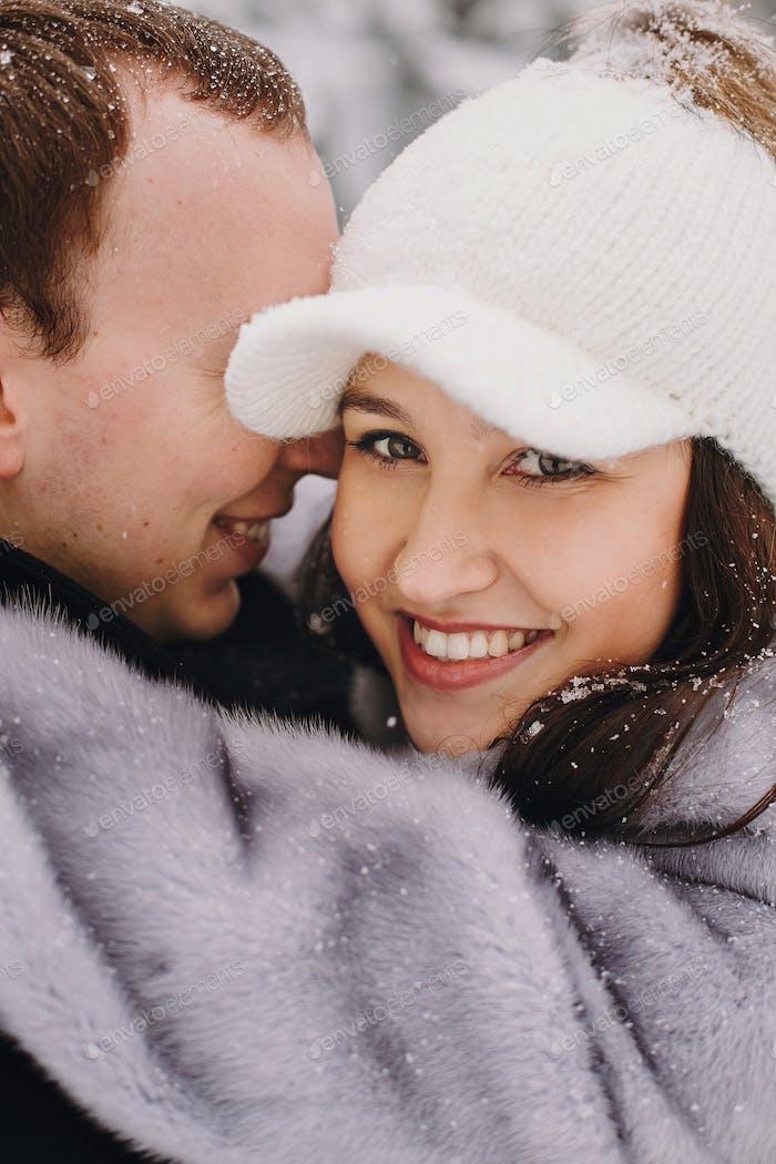 Porträts von fröhlichen romantischen Mann und Frau lächelnd und umarmen am Wasserfall im Schnee