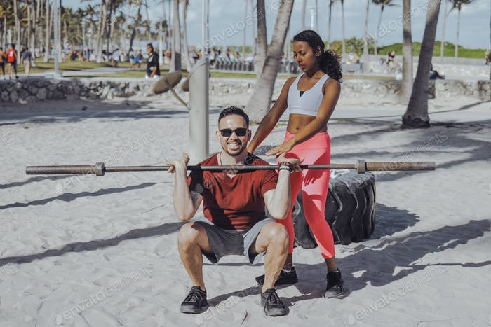 Woman helping man with workout on beach