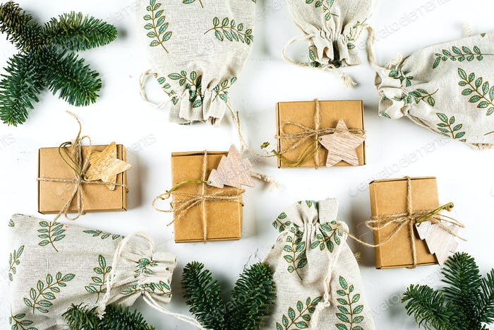 Christmas Craft Boxes and Pouches with fir branch on white background. Zero Waste Gift Wrapping