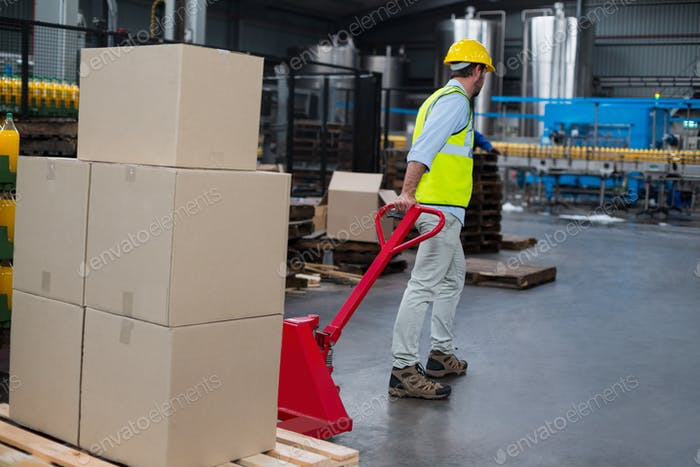 Factory worker pulling trolley of cardboard boxes