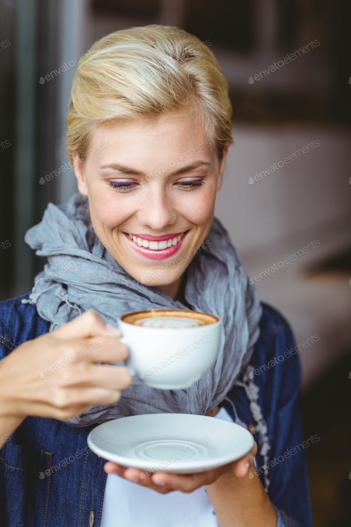 Smiling blonde enjoying a cup of cappuccino at the cafe