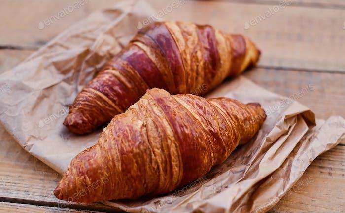 Delicioso croissant crujiente en un escritorio de madera.