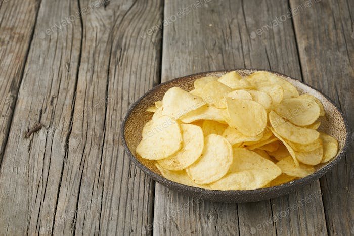 crisp in bowl, wooden background, closeup, copy space