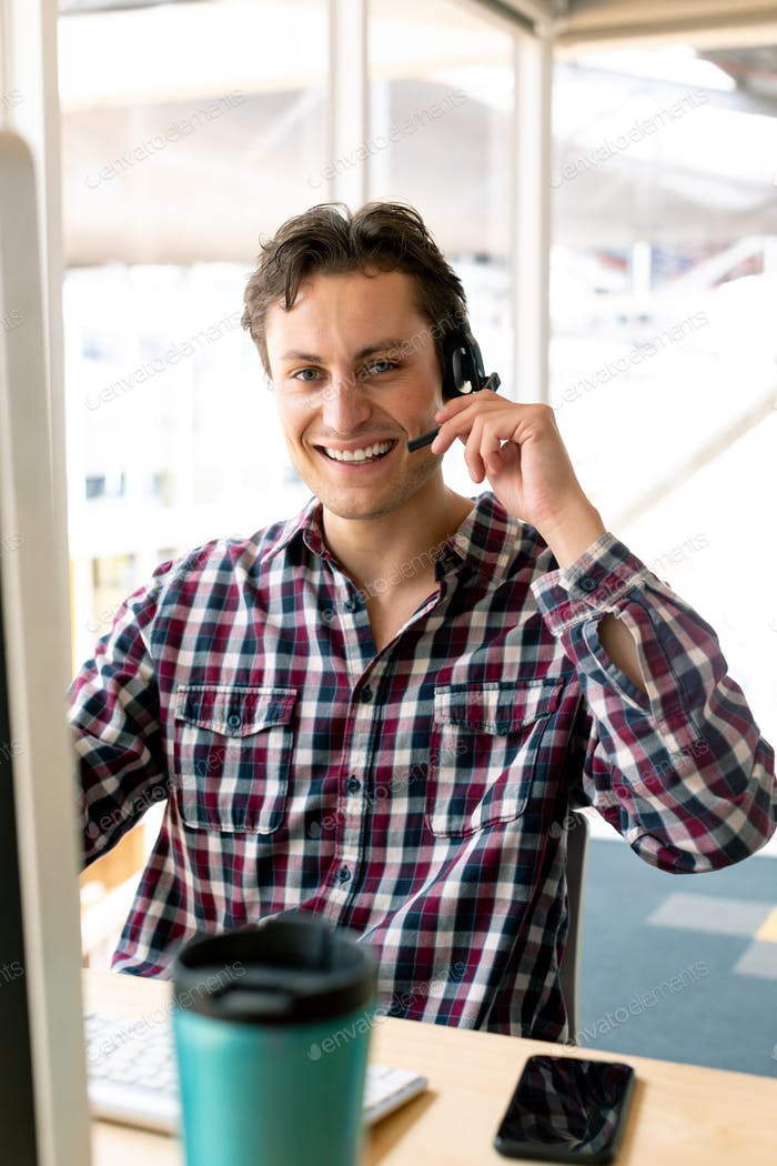Front view of Caucasian male customer service executive talking on headset at desk in office
