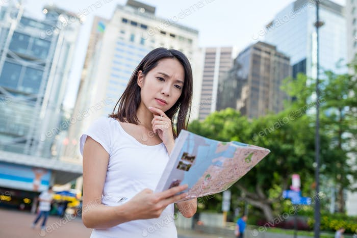 Woman use paper map to find location