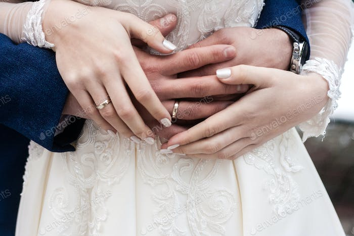 Hands of bride and groom with rings close up. Wedding and family concept.