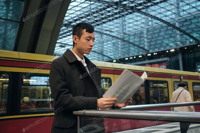 Young Asian businessman confidently reading newspaper at city subway station