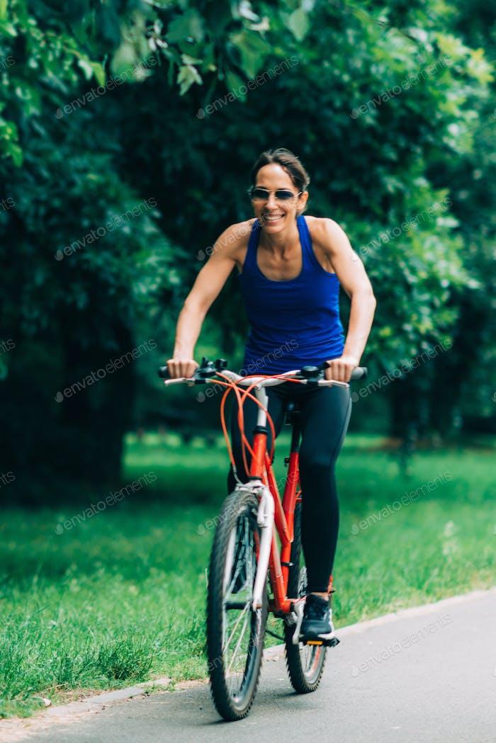 Frau Radfahren in einem park