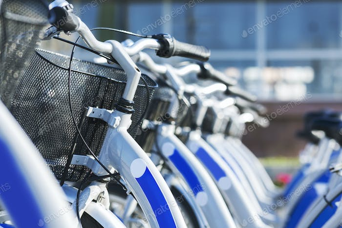 Similar blue bicycles for sharing parked outdoors