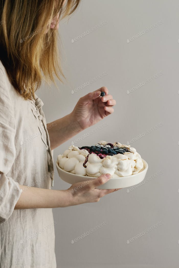 Meringue cake Pavlova in female hands