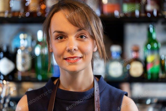 happy smiling barmaid or woman at cocktail bar