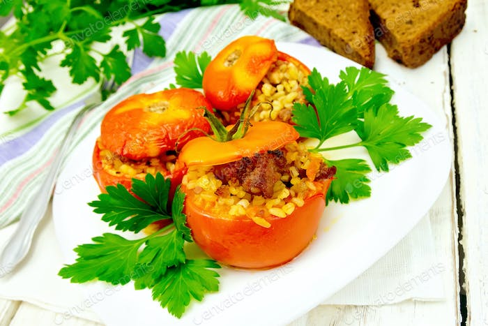 Tomatoes stuffed with bulgur and meat in plate on light board