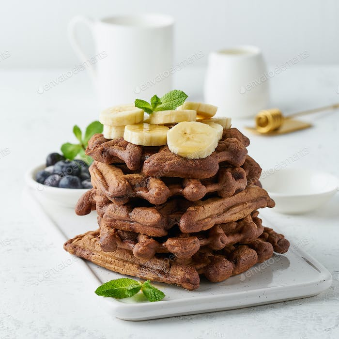 Chocolate banana waffles with maple syrup on white table, close up, side view.