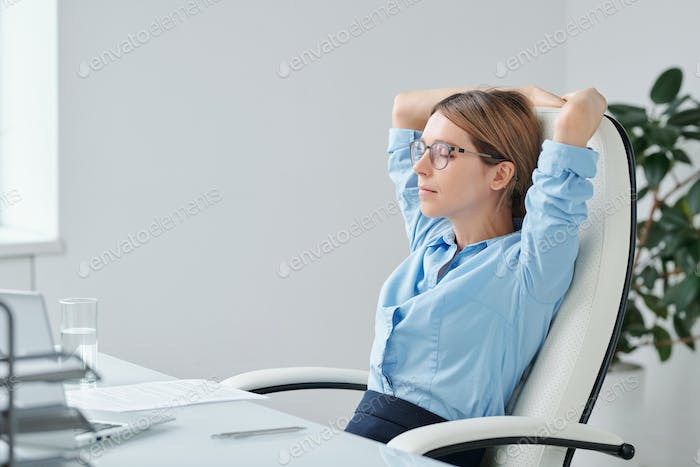 Young restful businesswoman keeping hands behind head while relaxing in armchair