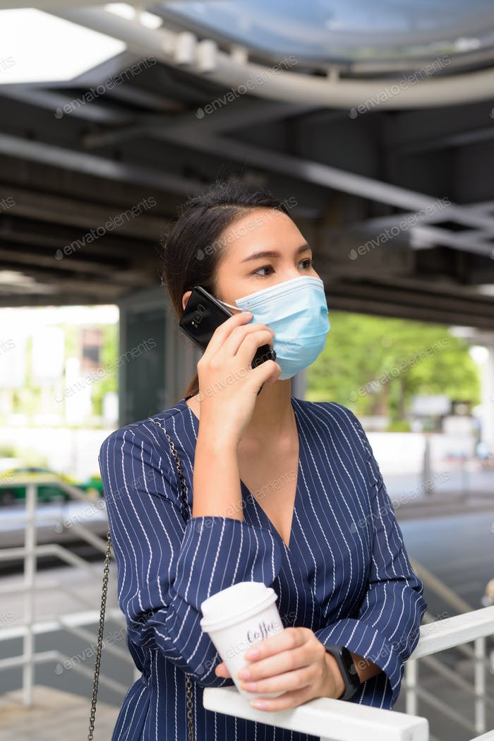Young Asian businesswoman with mask talking on the phone while having coffee on the go as the new