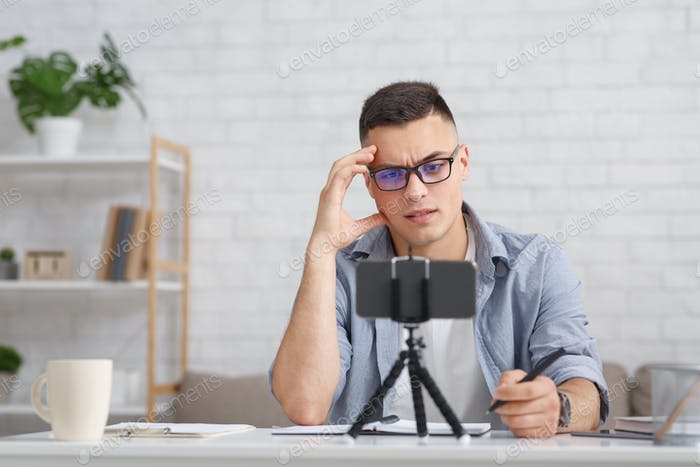 Webinar and online meeting. Pensive guy with glasses makes notes and watches webcam on smartphone